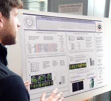 student discussing his research poster with Dr. Erdman